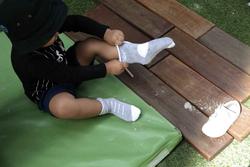 young child practicing putting on their shoes and socks